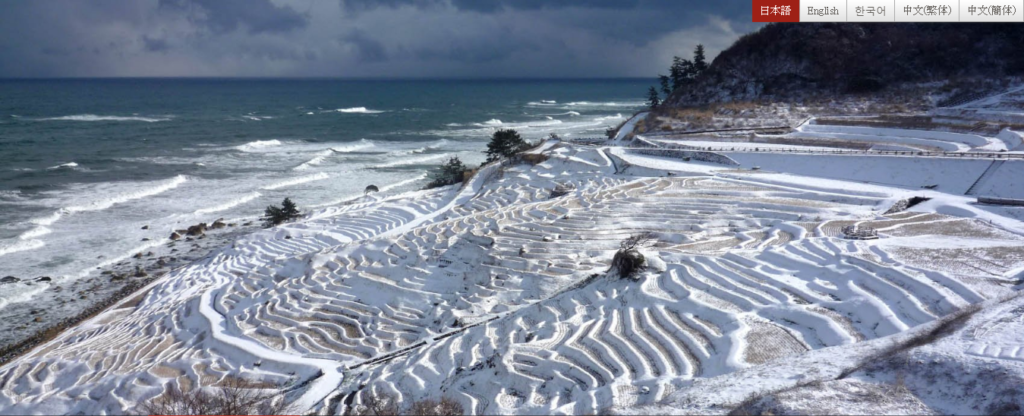 雪の白に覆われた棚田と日本海の荒波 - -石川県輪島市:白米千枚田- -